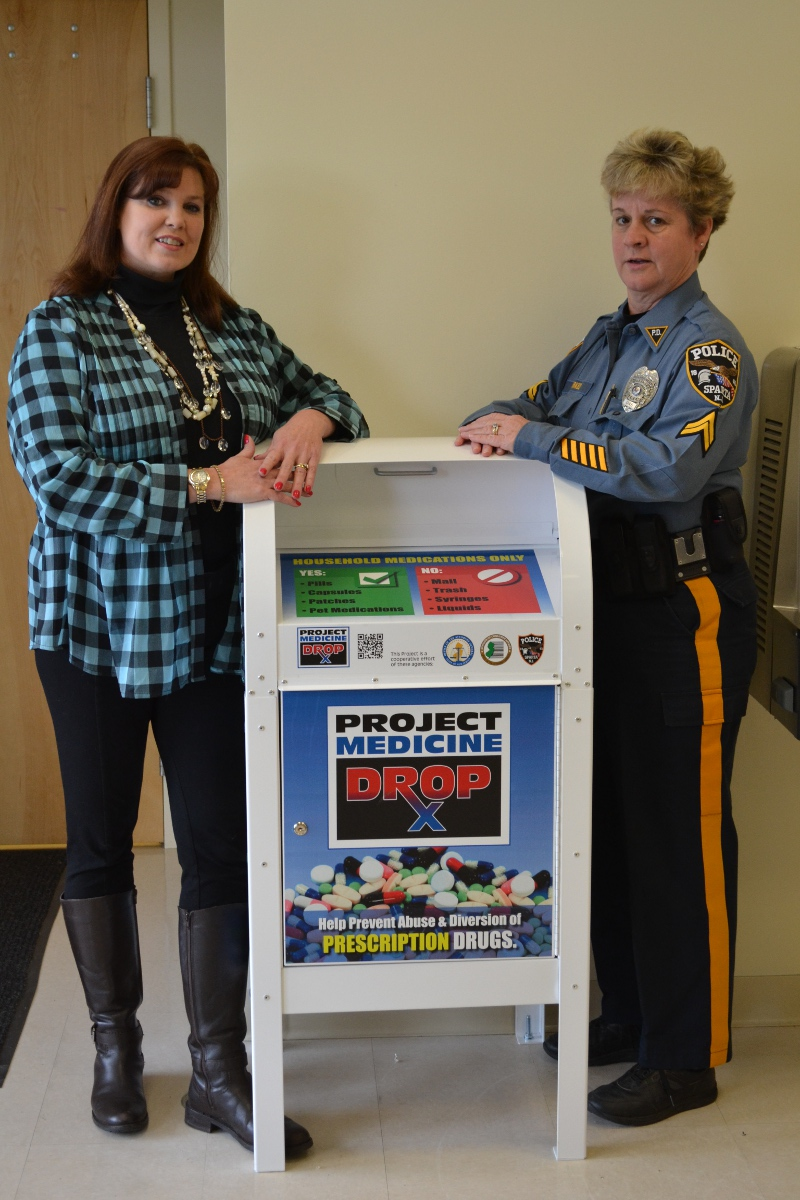 "Deputy Mayor Molly Whilesmith and Cpl. Susan Parkes stand next to the ""Project Medicne Drop Box"" after it was installed in the lobby of the Sparta Police Department last December.  The Drop Box has become a very easy and safe method for local residents to lawfully dispose of; unused, unwanted and expired medications. (Photo courtesy of the Sparta Township Police Department)"