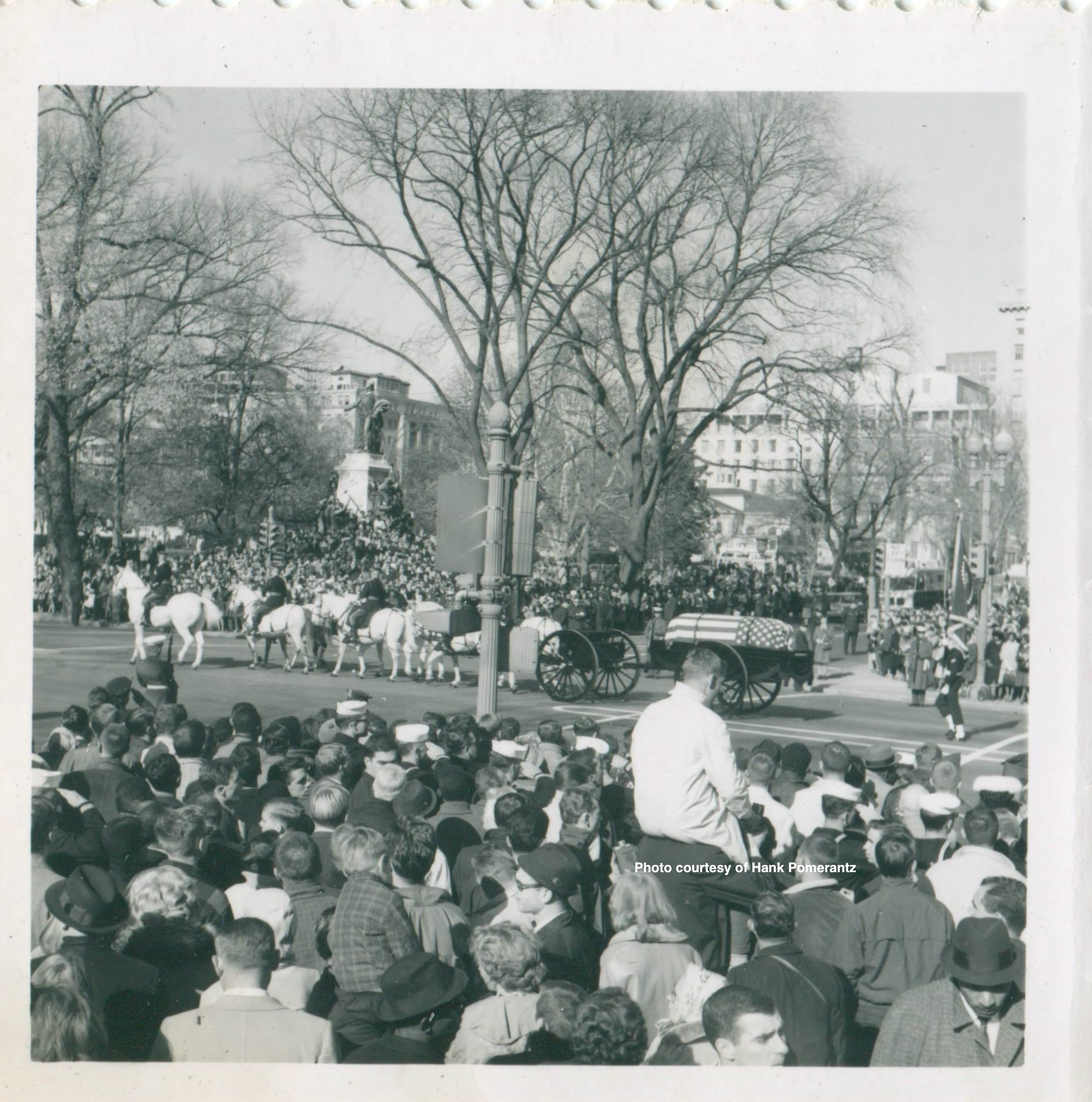 The crowd watches as JFK's casket is taken to the cemetery. Photo by and courtesy of Hank Pomerantz.