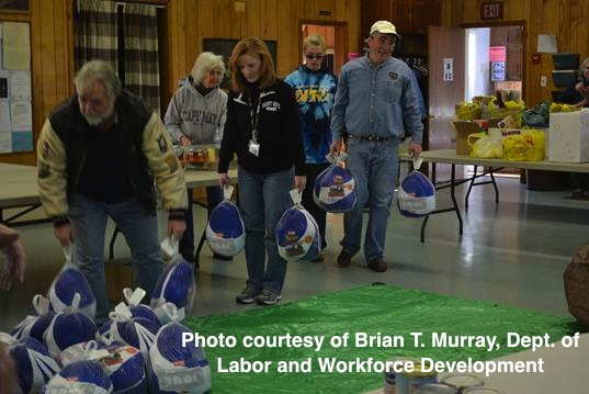 Volunteers, including New Jersey Labor Commissioner Hal Wirths, carry turkeys to the food bags. Photo courtesy of Brian T. Murray, New Jersey Department of Labor.