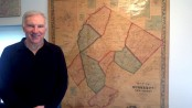 Bill Truran with his map of Sussex County, and arrowheads he has collected from the area.