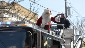 Santa Claus waves to spectators at the parade in Downtown Newton, atop the Tower 804 ladder truck.