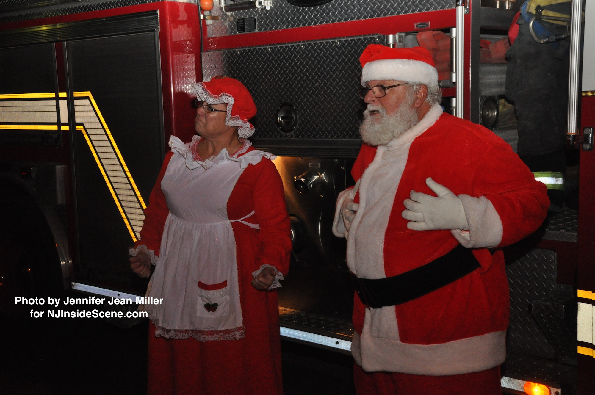 Santa and Mrs. Claus step off of the fire truck.