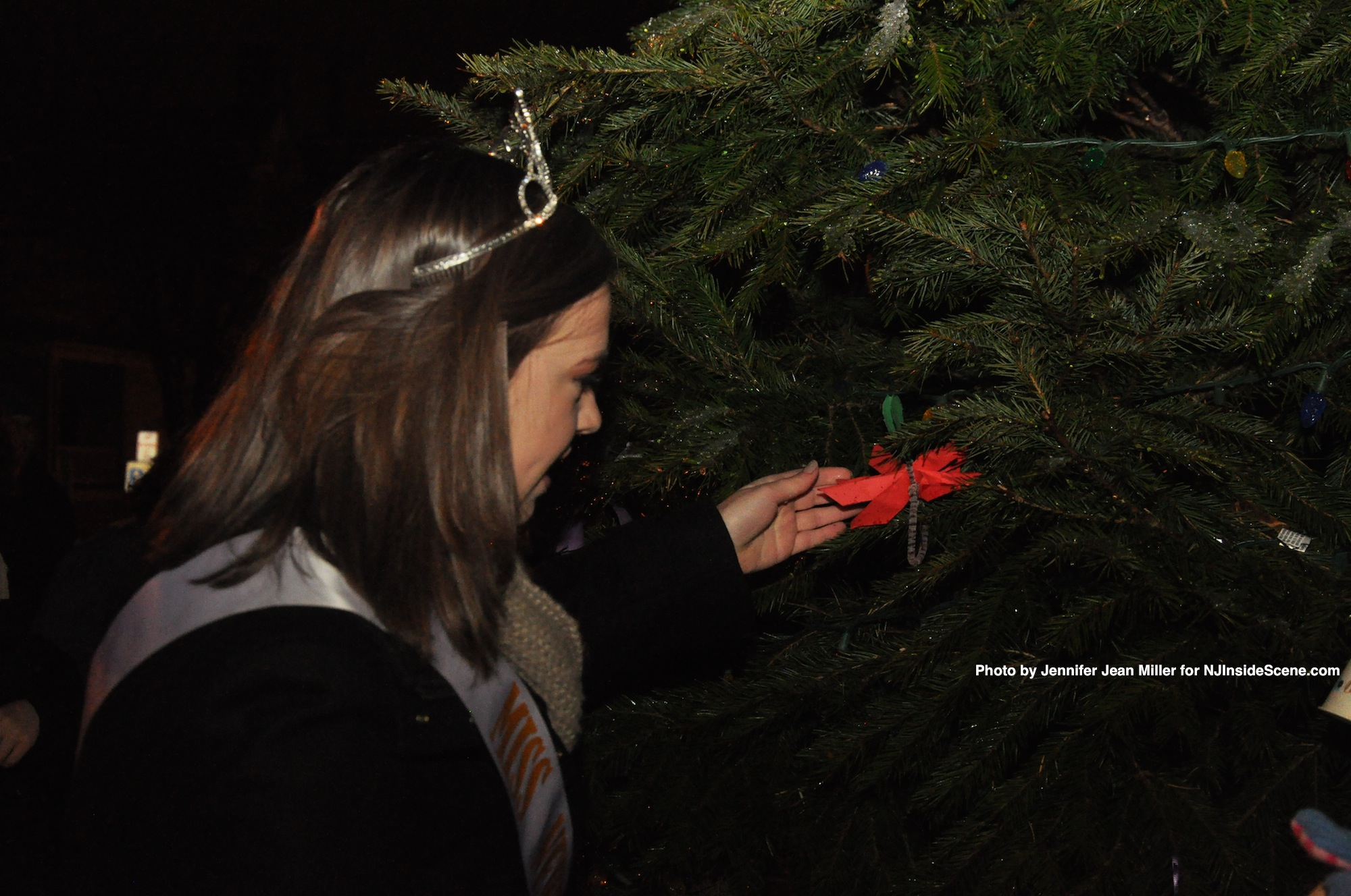 Miss Newton, Lauren Hennighan, helps to decorate the town's tree.