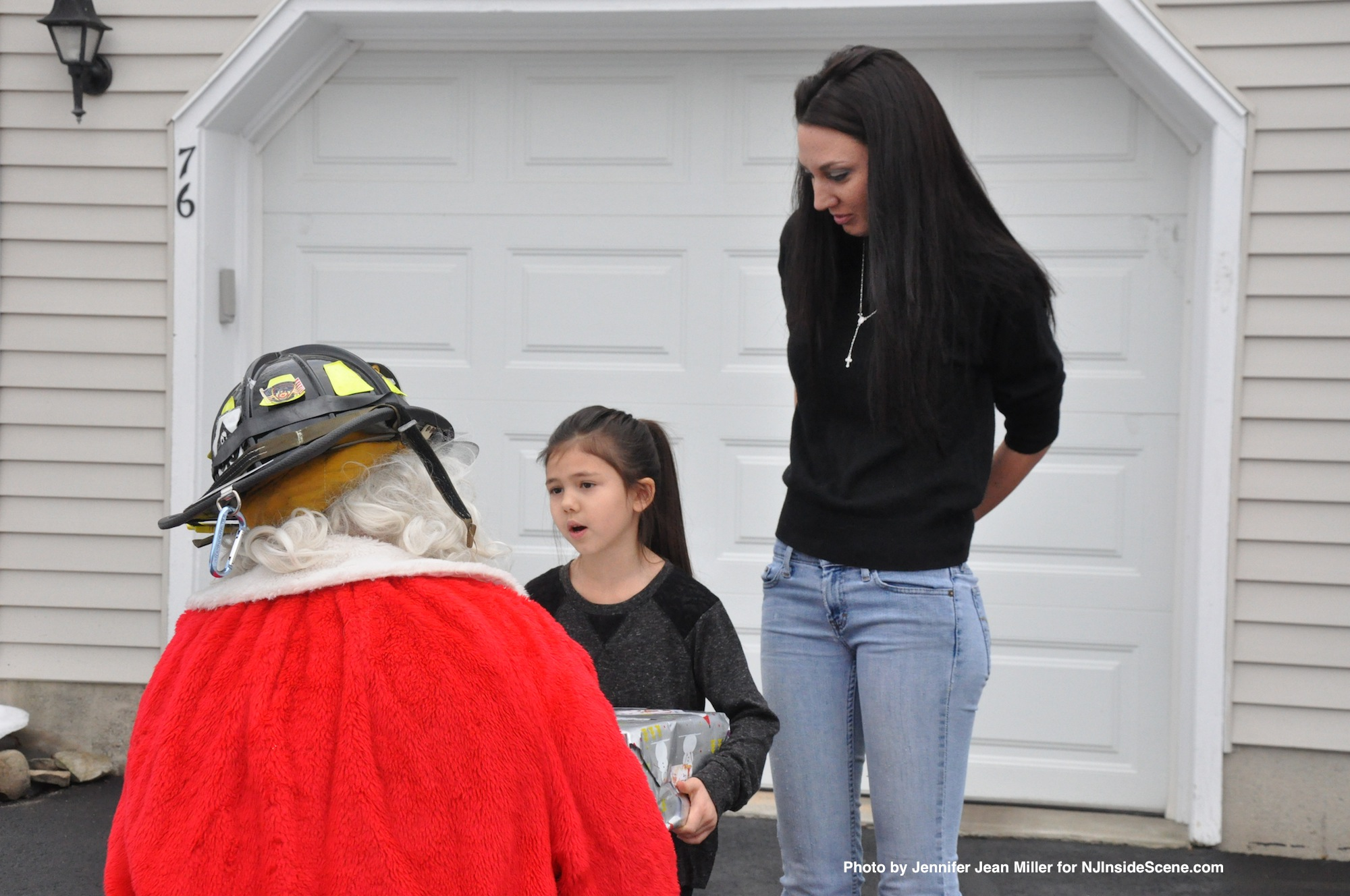 Andraya Serfin, age 6, speaks with Santa, as mom Amy looks on.