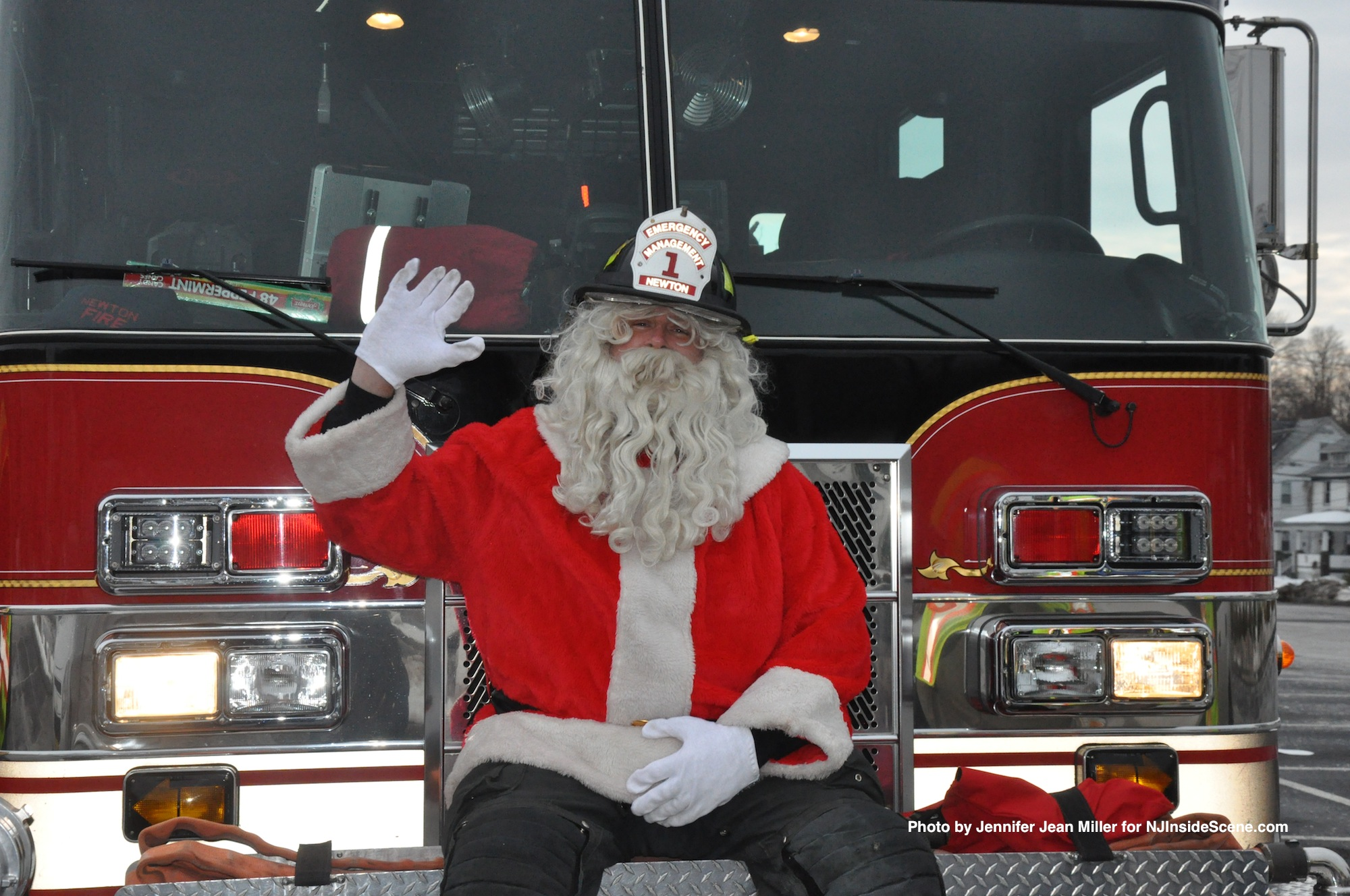 Santa smiles from the front of the fire engine.