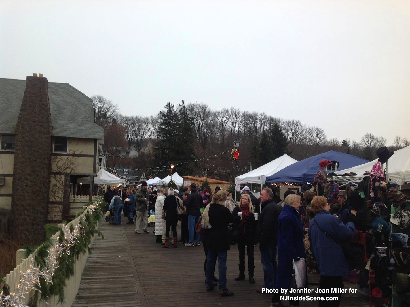 Attendees mingle on the Boardwalk during the Christmas Market, as snow begins to fall.