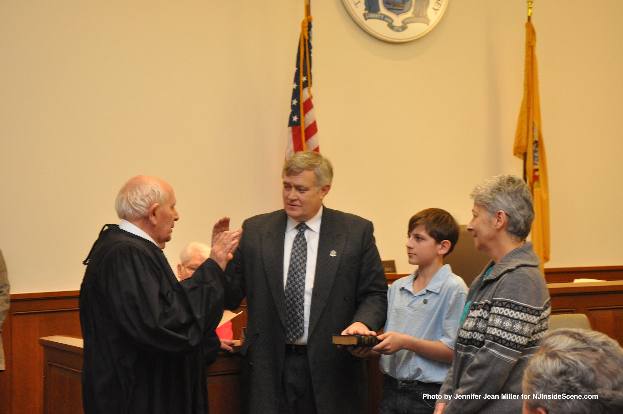 Judge Frederic Weber swears in George Graham, while Graham's wife, Gail, and grandson, Seth, look on.