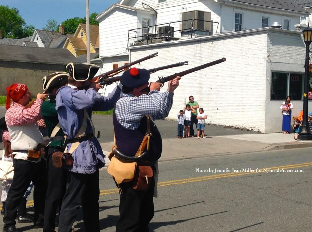 Rifles are fired in the air as part of the re-enactment during the parade. Photo by Jennifer Jean Miller.