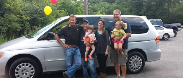 NAPA Sales Representative Jim Messina (left) and Elite Automotive owner Dave Hergert (right) congratulate Yolanda Dones and her family on the acquisition of a refurbished van as part of the auto donation program at Project Self-Sufficiency.