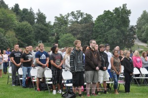 The audience during the memorial service, stands at attention as the flag is raised. Photo by Jennifer Jean Miller.