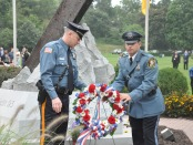 Newton Police Officer Scott King (left) and Hopatcong Police Officer Edward Janosko (right) carry the wreath to the monument. Photo by Jennifer Jean Miller.