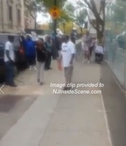 Protestors confront Burke from the sidewalk in this screenshot from the video. Image provided.
