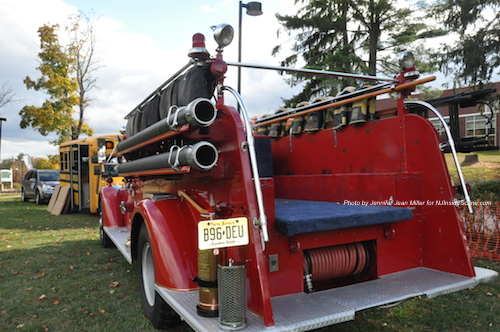 The Newton Fire Museum's antique Mack engine sits behind the bus for Stuff the Bus. The Newton Fire Museum was also a beneficiary of a portion of the entry proceeds.  Photo by Jennifer Jean Miller.