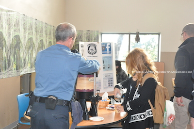Newton Police Officer Shawn Burke checks on the coffee pot during the event. Photo by Jennifer Jean Miller.