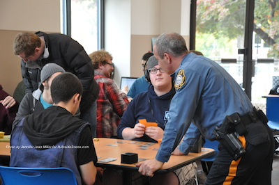 Newton Police Officer Shawn Burke visits a table of students at the Coffee with a Cop on Campus event at SCCC. Photo by Jennifer Jean Miller.