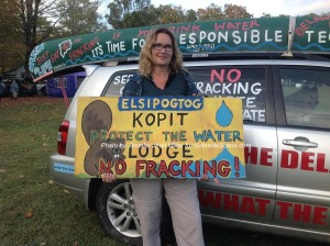 Elizabeth Nelson holds up her sign about the Elsipogtog Nation and stands in front of her anti-fracking mobile. Photo by Jennifer Jean Miller.