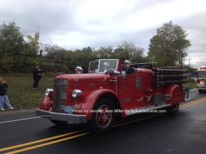 A vintage Beemerville Fire Truck includes Fred Space as a passenger. Photo by Jennifer Jean Miller.