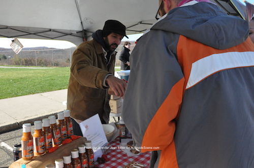 Austin D'Almeida offers samples of the Jersey Barnfire Hot Sauce to visitors at his booth. Photo by Jennifer Jean Miller.
