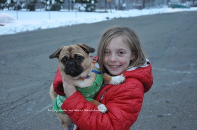 Molly McHose holds the 2014 Rein Dog, her puppy Sergeant the Pug and Pekingese mix. Photo by Jennifer Jean Miller.