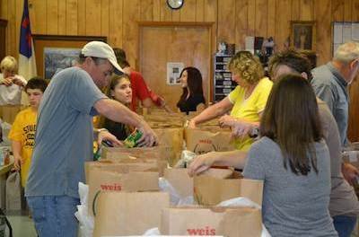 Labor Commissioner Harold J. Wirths helps volunteers at the Sussex United Methodist Church bag complete Thanksgiving dinners that will be distributed to families in need through the Sussex Help Center. Photo courtesy of the New Jersey Department of Labor and Workforce Development.