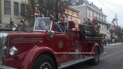Santa waves to one side of the crowd along the sidewalk. Photo by Jennifer Jean Miller.