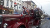 Santa waves from atop the vintage Newton Fire Truck in the holiday parade. Photo by Jennifer Jean Miller.