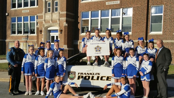 Nevin Mattessich, right, President of FOP Lodge 57, and Franklin Police Officer Rafael Burgos (left), along with the Franklin Varsity Cheerleaders. Photo courtesy of FOP Lodge 57.