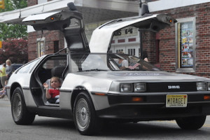 A young parade participant waves from a DeLorean. Photo by Jennifer Jean Miller.