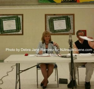 Parker Space (right) holds up the report for public viewing as Gail Phoebus (left) looks on. Photo by Debra Jane Ramirez.