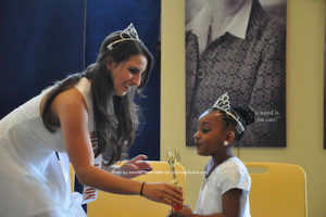 Miss Newton 2014 Emilie Petry presents Little Miss Newton 2015 Zariah Moore with her gifts for winning the title. Photo by Jennifer Jean Miller.