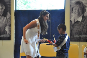 Miss Newton 2014 Emilie Petry presents items to the winner of Little Mr. Newton 2015 Rodolfo Sarmiento Romero. Photo by Jennifer Jean Miller.
