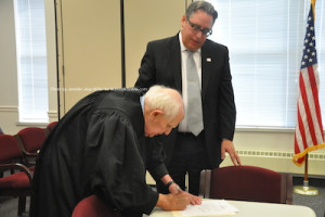 The Honorable Judge Frederic Weber signs after swearing in John D. Williams. Photo by Jennifer Jean Miller.