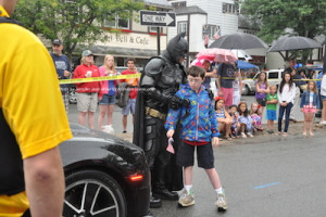 Batman stops to pose for photos with a young spectator. Photo by Jennifer Jean Miller.