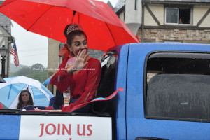 The Queen of the Fair waves to parade attendees in between raindrops. Photo by Jennifer Jean Miller.