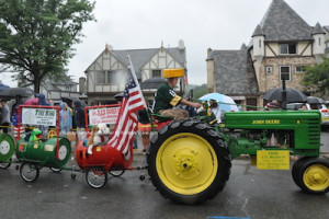 One of the tractors towing along sponsors in a line of carts. Photo by Jennifer Jean Miller.
