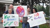 Locals hold up their signs against Taco Bell before entering the meeting at the Newton Municipal Building about the proposed site plan. Photo by Jennifer Jean Miller.