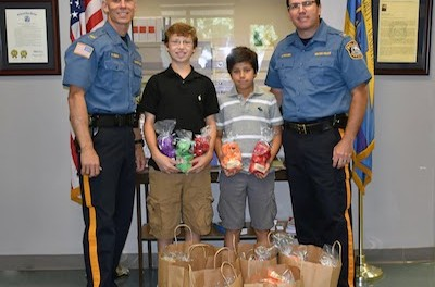 (Left to right) are Lt. Robert E. Osborn, Jr., Stefano Montalvo, Sebastian Montalvo and Chief Mike Richards in the lobby of the Newton Police station. Image courtesy of the Newton Police Department.