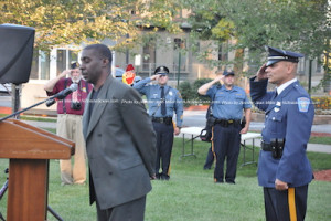 Arthur Sibblies, retired Newton Police Officer, sings the National Anthem. Photo by Jennifer Jean Miller.