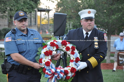 Newton Patrolman Mahir Kaylani (left) and Newton Fire Department's Jason Miller (right) carry the wreath in remembrance of 9/11 victims. Photo by Jennifer Jean Miller.