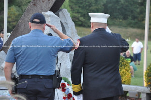 Patrolman Mahir Kaylani (left) and Newton Fire Chief Jason Miller (right) salute after placing the wreath at the foot of the memorial. Photo by Jennifer Jean Miller.