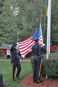 Officers lower the flag. Photo by Jennifer Jean Miller.