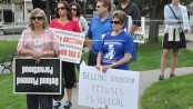 Participants stand with signs in Newton's green. Photo by Jennifer Jean Miller.