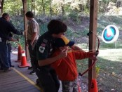 Stephen R. helping a scout properly hold a bow. Image courtesy of Venture Crew 276.