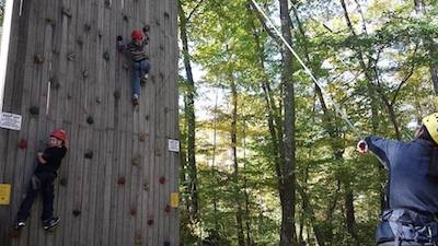 Katie R. helping scouts on the rock climbing wall. Image courtesy of Venture Crew 276.