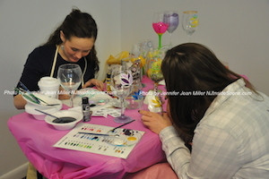 One of the vendors during the event with creates hand-painted glassware with attendees. Photo by Jennifer Jean Miller.