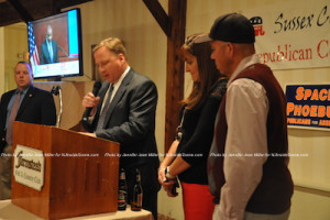 Sussex County Republican Chairman Jerry Scanlan announces results at the podium while Sheriff Michael Strada (left) and Jill and Parker Space (right) look on. Photo by Jennifer Jean Miller.