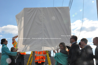 Senator Littell's family begins pulling back the cover to reveal the sign made in his memory. Photo by Jennifer Jean Miller.
