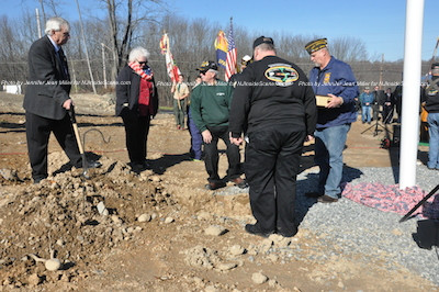 John Harrigan places the first mound of dirt on the plot. Photo by Jennifer Jean Miller.