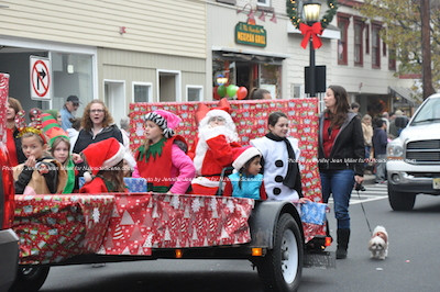 Festive elves make their way down Spring Street aboard a float. Photo by Jennifer Jean Miller.