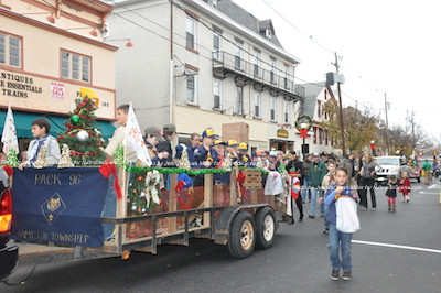 Scouts wave from the float and toss out candy. Photo by Jennifer Jean Miller.